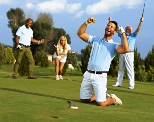 Happy golfer kneeling at hole with raised fists after putting in