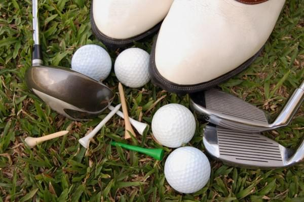 Golf shoes and equipment on the grass