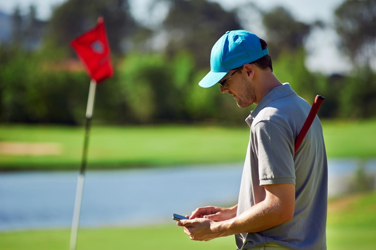modern golf man with smart phone taking score on mobile gps devi