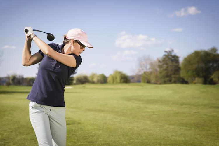 Close up of woman golf player swinging golf club